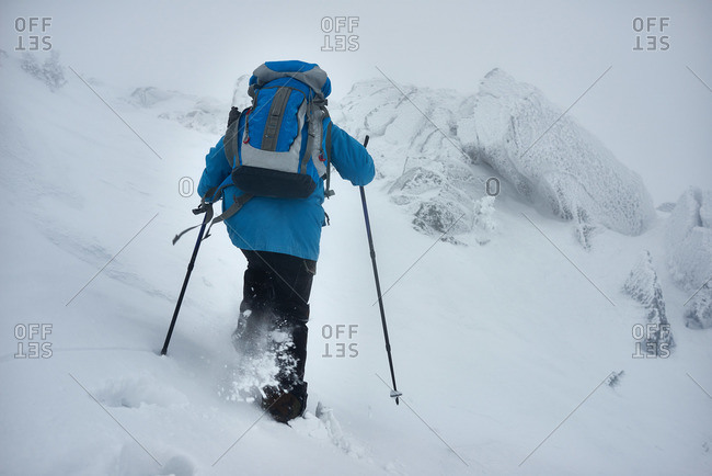 Rear view of female hiking among snow