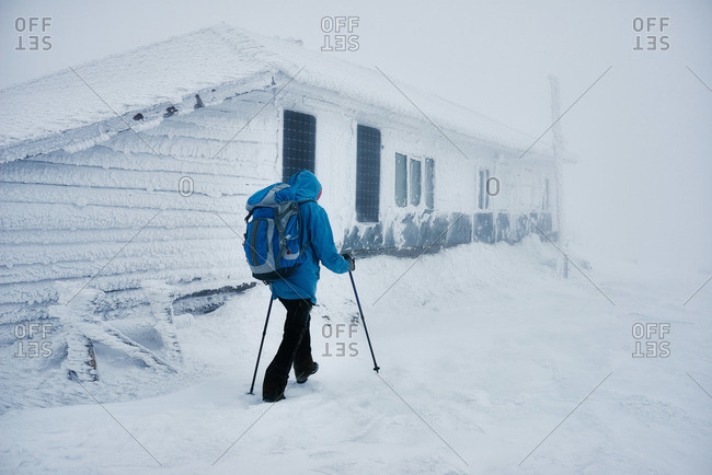 Hiker passing snowy building