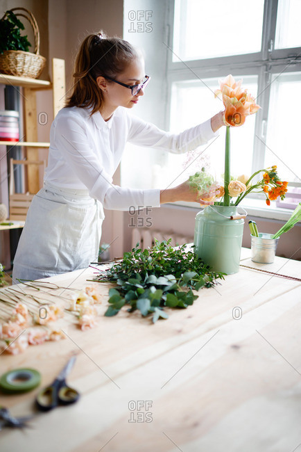 Florist putting flowers into metal vase