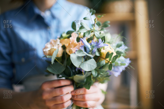 Florist holding a bouquet in a flower shop