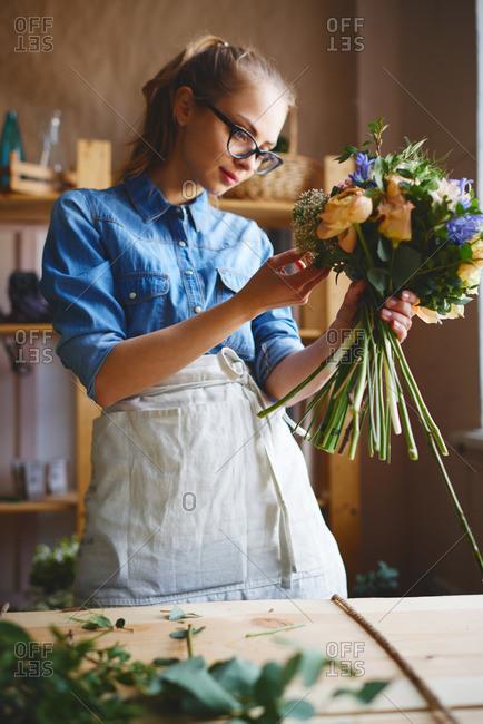 Woman creating a large floral arrangement