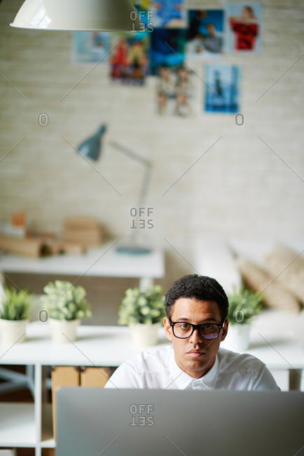 Young businessman looking up from his work computer