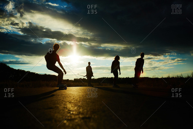 Young people longboarding outside in the evening