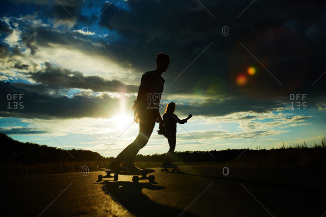 Teenagers longboarding in the evening