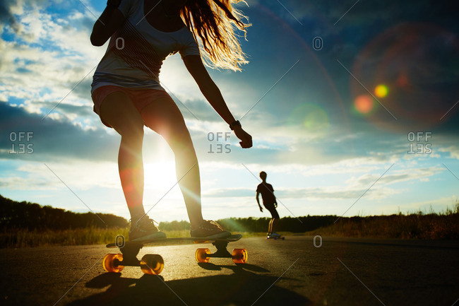 Active girl longboarding with friends