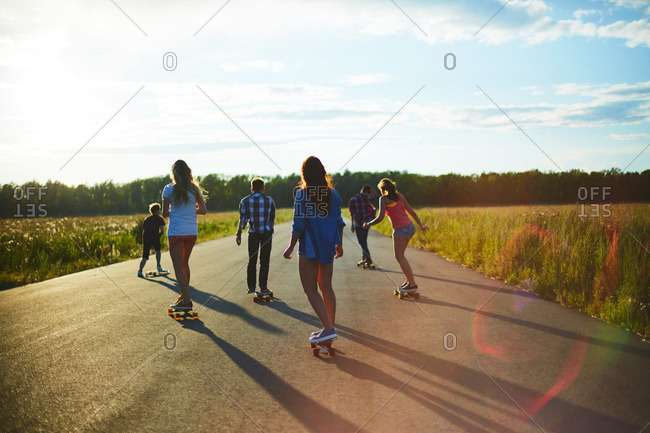 Group of active teens longboarding together