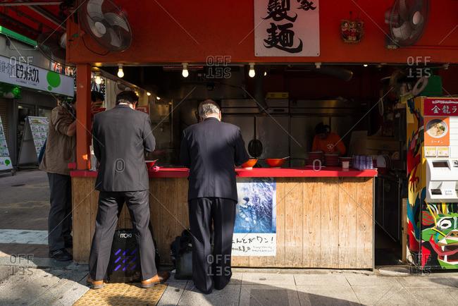 Dotonbori, Osaka-shi, Osaka-fu, Japan - December 2, 2015: Men at street food stand, Japan