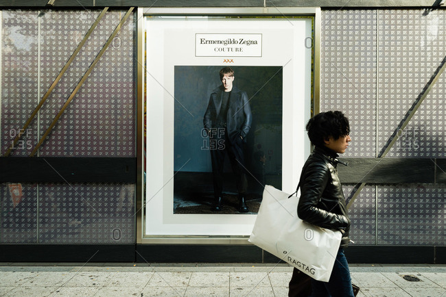 Shinsaibashisuji, Osaka-shi, Osaka-fu, Japan - December 2, 2015: Hip man walking past ad, Japan