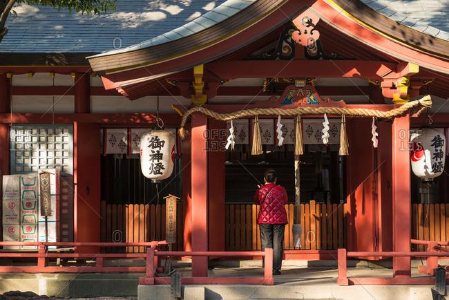 December 2, 2015: Woman outside traditional temple, Osaka Japan