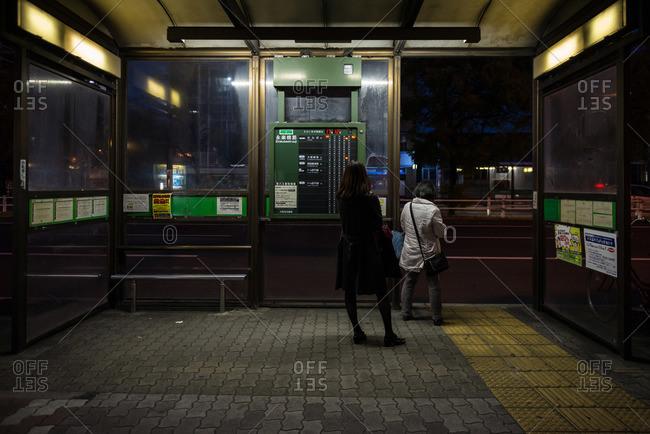 Women in bus shelter, Osaka, Japan
