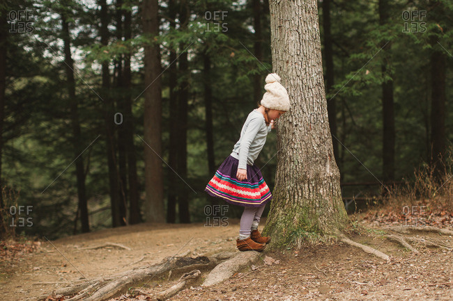 Little girl playing on tree roots