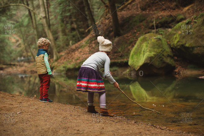 Brother and sister playing with a stick in a creek