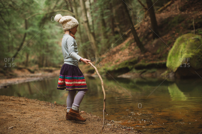 Little girl standing beside a stream in the woods