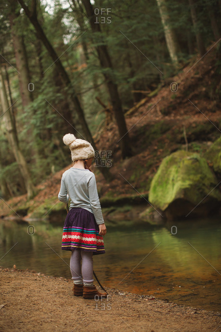 Little girl looking into a stream in the woods