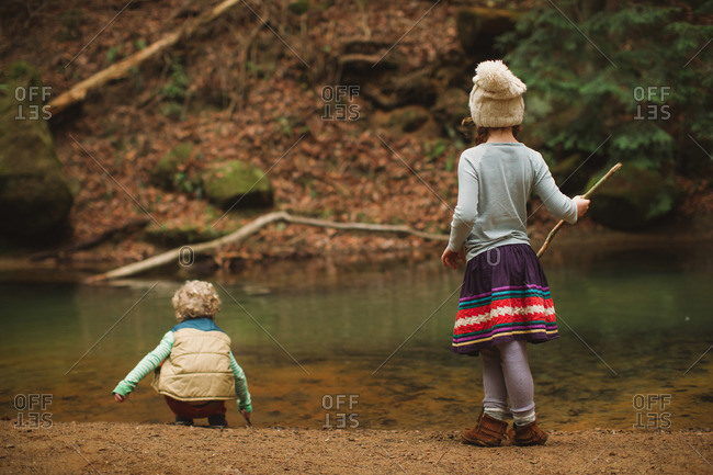 Little girl and boy playing beside a stream in the woods