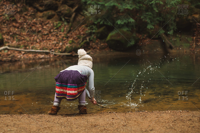 Little girl splashing in a creek with a tree branch