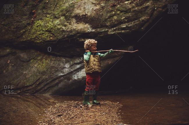 Little boy standing in the middle of a stream taking aim with a stick