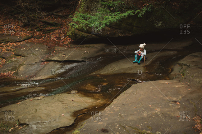 Little girl sitting on a rock in the middle of a creek