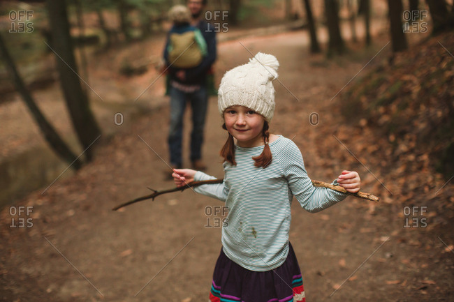 Little girl standing on a nature trail propping her arms on a stick