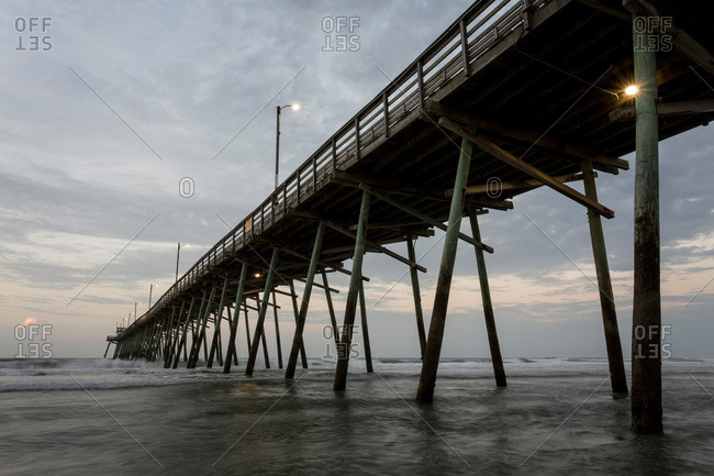 Waves crashing under a pier at sunset, Emerald Isle, NC