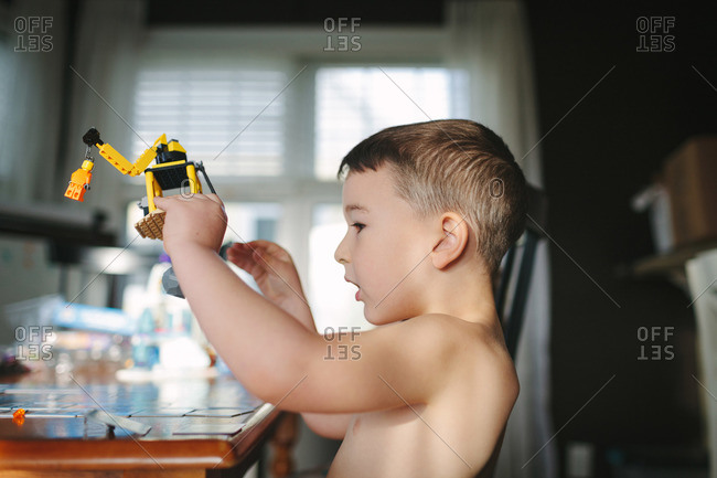 Little boy playing with a plastic toy crane