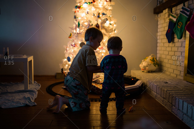 Little boys playing in front of a white Christmas tree