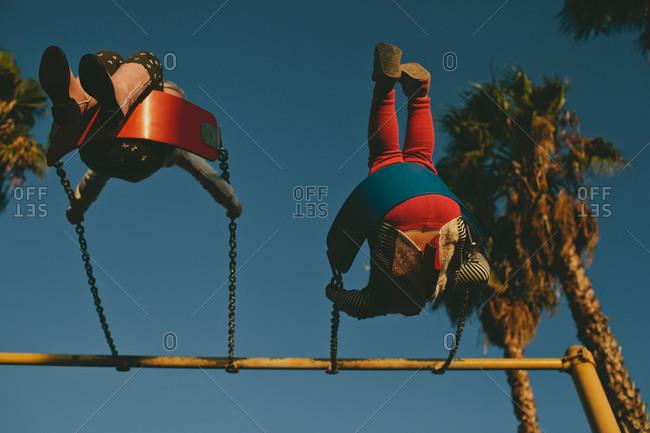 Underside of two girls on a swingset