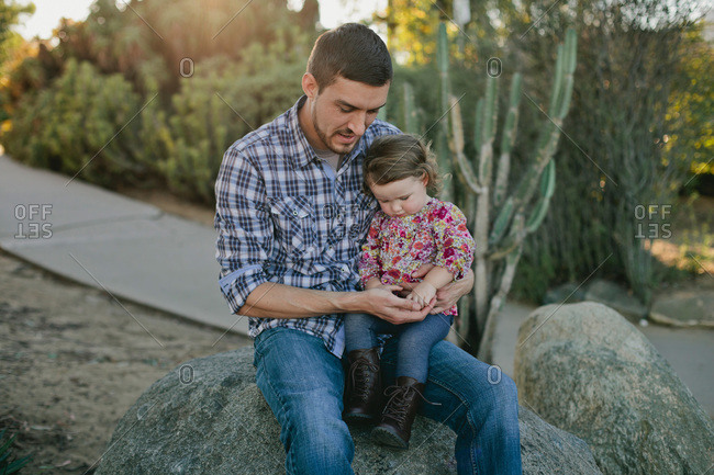 Father and daughter sitting together on a rock