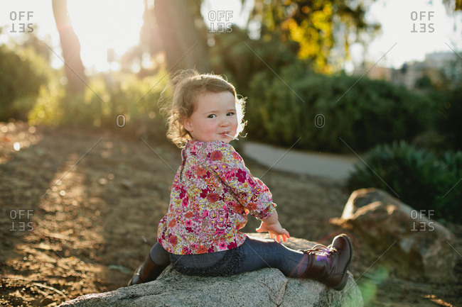 Little girl sitting on a rock eating a lollipop