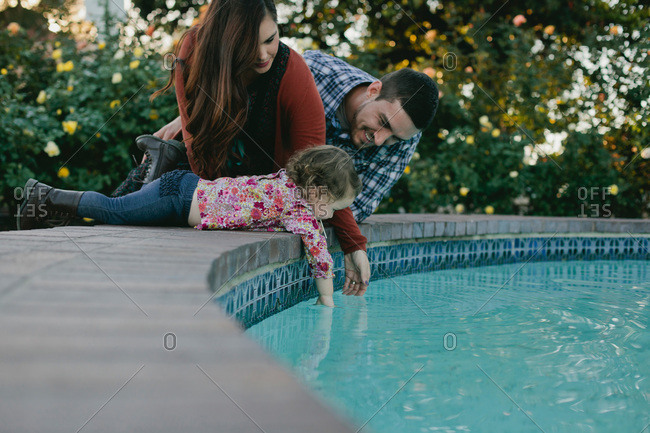 Little girl with her parents lying at the edge of a fountain