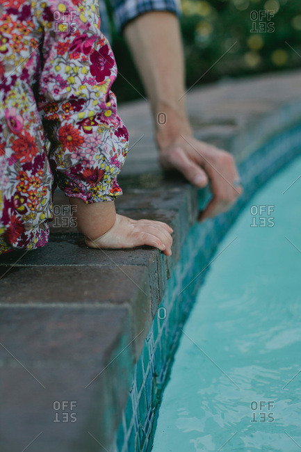 Hands of a little girl and her father on the edge of a fountain