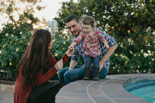 Little girl playing with her parents on the edge of a water fountain
