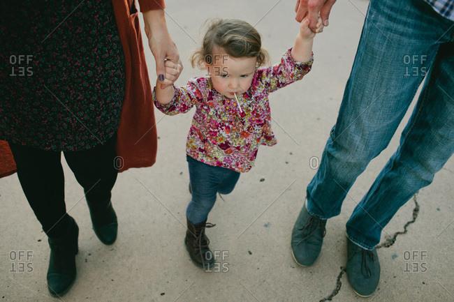 Little girl standing between her parents holding their hands