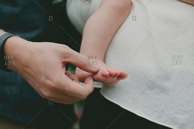 Father touching his baby son's bare foot