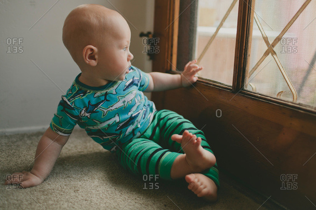 Baby boy looking out of a wooden door