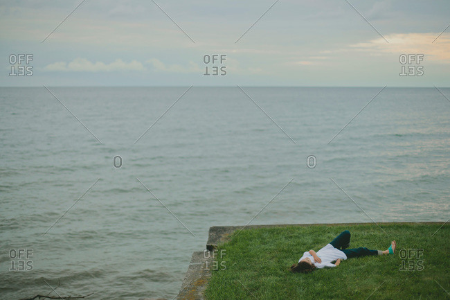 Young woman lying on the edge of a lawn overlooking the ocean