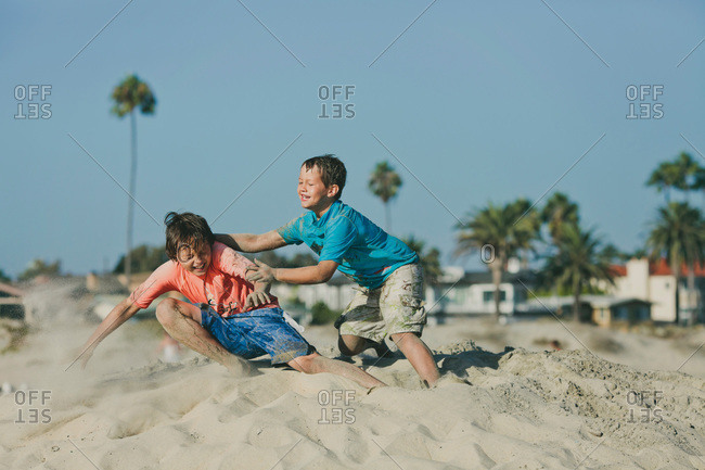 Two brothers playing on a beach