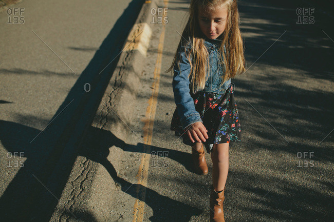 Little girl walking on a paved road