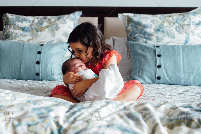Girl kissing newborn on bed
