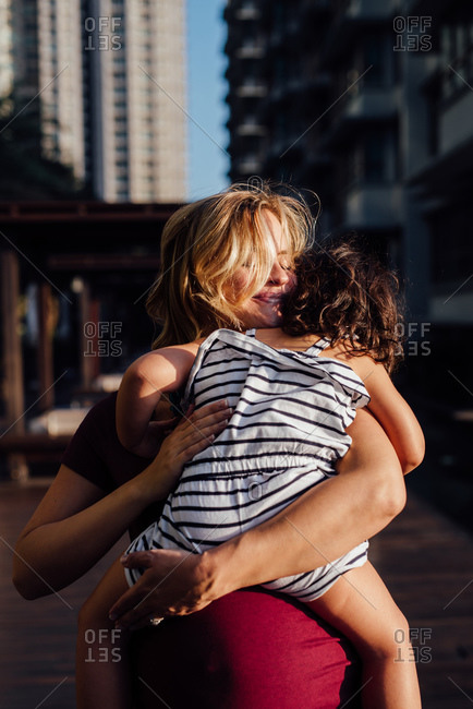 Pregnant mom embracing a girl