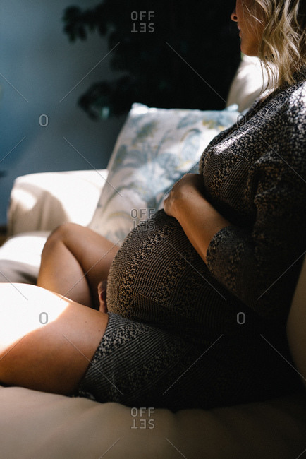 Pregnant woman holding belly on couch
