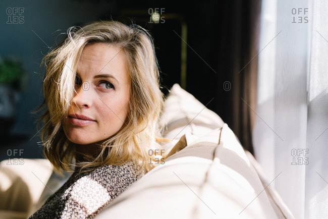 Blonde woman on couch in sunlight