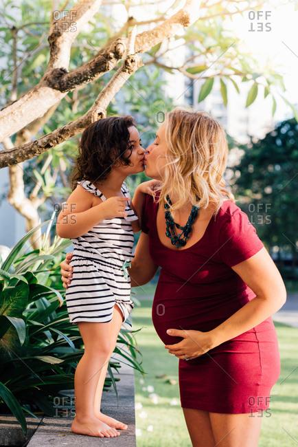 Girl kissing pregnant mother