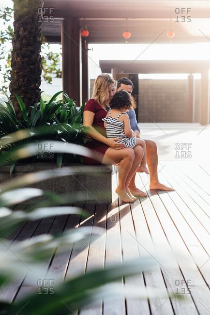 Family sitting on deck ledge together