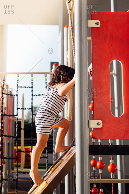 Girl walking up playground ramp