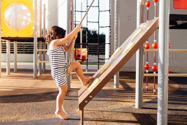 Girl climbing jungle gym rope