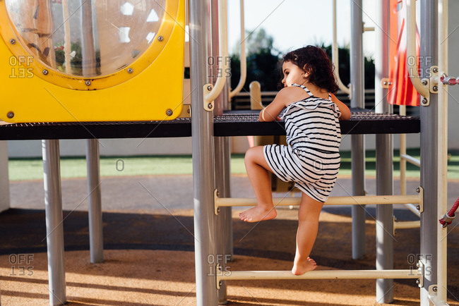 Girl climbing steps of jungle gym