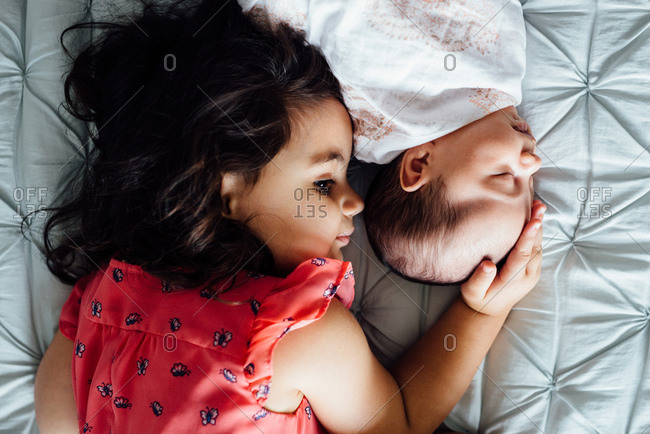 Girl lying next to newborn on bed