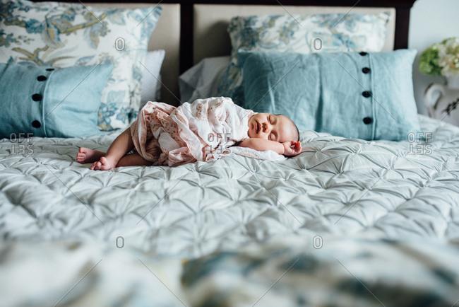 Baby sprawled asleep on bed