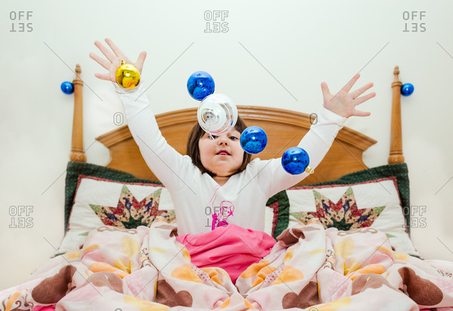 Girl in bed tossing Christmas ornaments